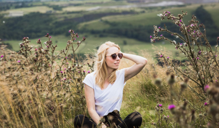 woman sitting in the thistle weeds thinking about a drink less lifestyle